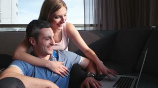 Attractive Couple Using A Laptop on couch