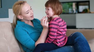 Attractive woman teaches her daughter how to put on lipstick