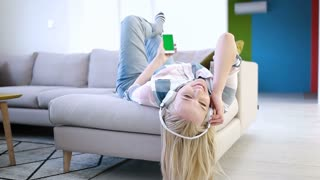 Beautiful blonde Woman Listening To Music headphones On Couch At Home Relaxing