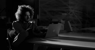 black and white video of Man surfing the net. Concept of man working overtime.