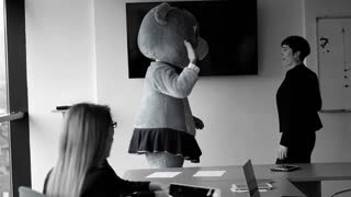 Boss dresed as teddy bear having fun with bussines people in modern corporate office, black and white