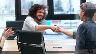 Business Partners Shaking Hands At Meeting Table