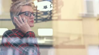 Casual businesswoman standing next to window & talking on cell phone in city office