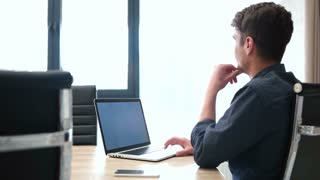 Casual Successful Businessman Working Alone In Boardroom Of City Office