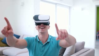 Caucasian hipster man in casual shirt using his VR headset at home in the living room. Close up