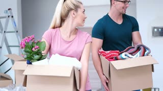 Couple Carrying stuff Into New Home On Moving Day