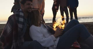 Couple having fun with friends beside bonfire on beach party