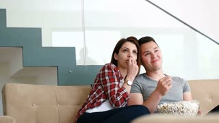 Couple In Living Room Watching Television Together