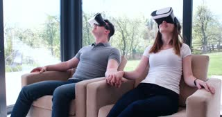 Couple of young woman and man using virtual reality glasses at home
