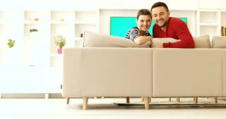 Couple relaxing in sofa, having some free time together with green screen tv in background