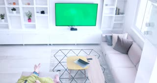 Couple Sitting Together In Front Of The Television with green screen and using devices with green screen