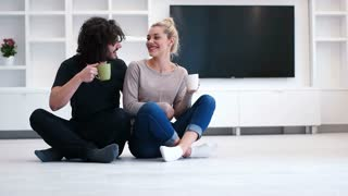 Couple Take A Coffee Break From Unpacking Boxes In New Home
