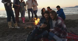 Couple using cell phone during beach party with friends drinking beer and having fun