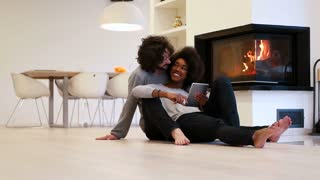 Cute Couple Get Cozy By Fireplace And using Tablet at modern home