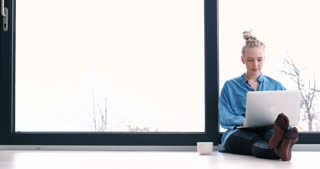 Cute Young Woman Sitting On Floor in willa  By Window Using Laptop