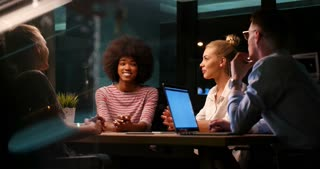 Diverse Business Team In Late Night Boardroom Meeting In Contemporary Office