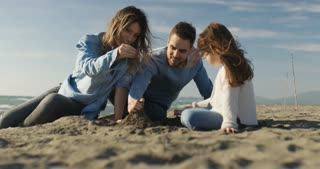 Family with kids resting and having fun at beach during autumn