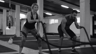 Fit Couple Exercising in modern gym