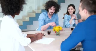 Group Of Casual Business People Discussing During Business Meeting in bright startup office