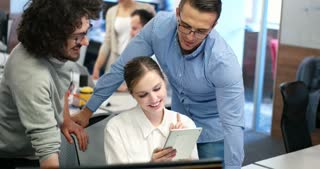 Group of happy young business people using tablet while meeting at office