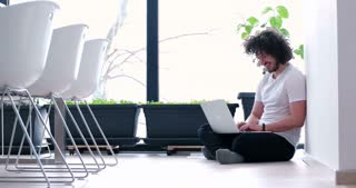 Handsome Young Man with afro hair Sitting on Floor and Using His Laptop While Relaxing At Home