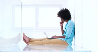 Happy African woman using laptop at foor in new apartment
