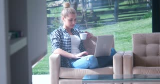 Happy casual beautiful woman working on a laptop and drinking coffee while sitting on the sofa in the house.