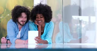 Happy couple watching videos or sharing media content from a tablet
