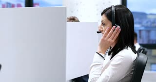 Hot-line operators with headphones consulting clients in call center