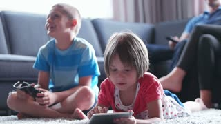 kids in living room using technolgoy, brother palying video games while his sister uses tablet