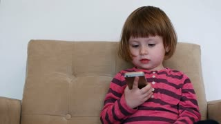 Little Girl Using Smart Phone. Child Playing With Smartphone