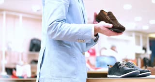 Man Chooses Shoes At Shoe Store