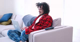 Man on sofa relaxing with laptop