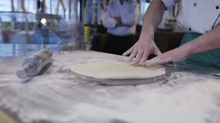 Man Rolling Out Pizza Dough In A Pizzeria