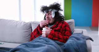 Man With Flu At Home Takes Temperature