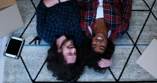 Multiracial Couple Relaxing Lying On The Floor After Moving To New Apartment