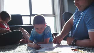 parents and kids colouring together at home in living room