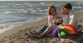 Parents Having Happy Time With Children On The Beach