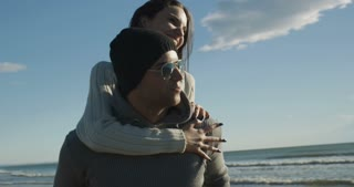 Piggy Back Lovers on beach at beautiful autumn day