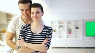 Portrait Of Happy Couple Standing in New Home with green screen TV