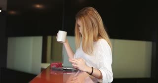 Real Woman Using Mobile Phone At Home Drinking Coffee Enjoying Relaxing