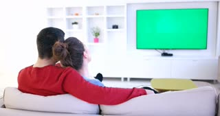 Rear view of Caucasian couple watching television with green screen in living room