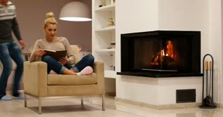 Romantic Couple By The Cozy Fireplace reading book