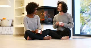 Romantic mixed race Couple By The Cozy Fireplace drinking coffee or tea