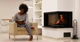 Romantic mixed race Couple By The Cozy Fireplace reading book