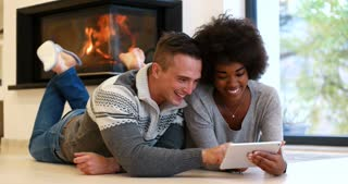 Romantic mixed race Couple By The Cozy Fireplace using tablet