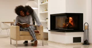 Romantic multiracional couple sitting by fireplace at home and reading the book
