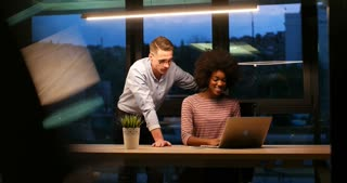 Smiling businessman and businesswoman talking and brainstorming late night at modern office