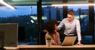 Smiling businessman and businesswoman talking late night in modern office