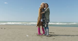 Two Cute Young Women Are Smiling And Enjoying Life at Beach on autumn day
